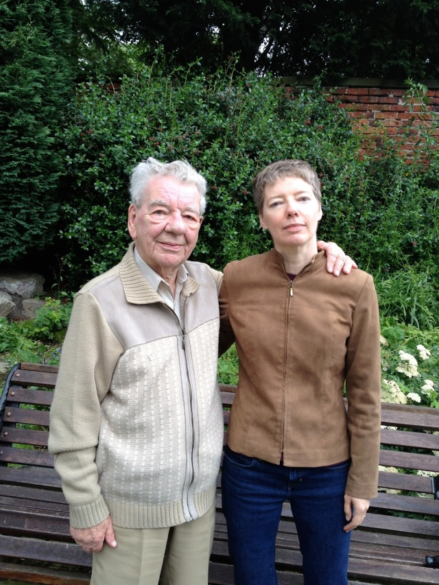 Colour photo of father and daughter circa 2012. They stand side by side. The man has white hair the woman's short hair is pale brown. They are the same height.