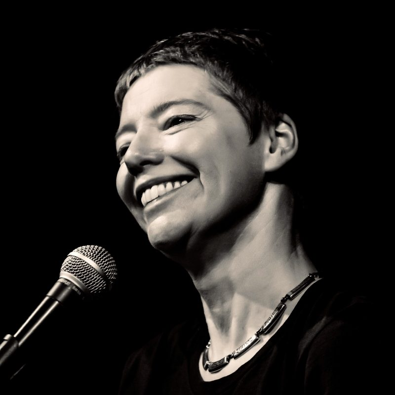 Image description: Black and white headshot of a smiling, short-haired white woman in three-quarter profile before a microphone. She looks very happy to be in front of an audience.