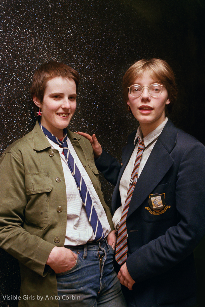 Two young women standing in close contact in front of a mica-flecked black wall. It's clear they are lovers. Both are wearing school ties, pale shirts, and jeans. Both only wear one earring each in the right ear. Carol, on the left, has short dark hair and a green, surplus army jacket. Nicola, on the right, has short fair hair, glasses, and a school blazer; she is wearing a double women's-sign pin as a tie clip. Their pupils are very slightly dilated.