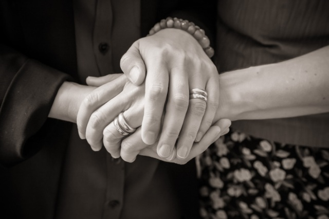 Sepia-tone photo of two women holding hands, wearing identical wedding rings