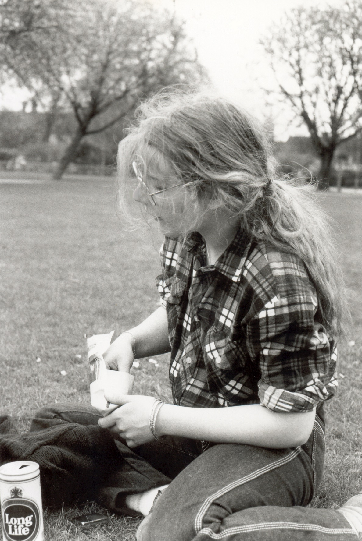 Black and white photo of teenage girl sitting on the grass and rolling a cigarette. She has long hair, tied back, gold-rimmed glasses, and there's a can of Long Life beer beside her.