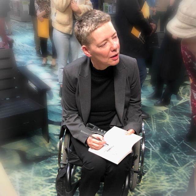 A short haired white woman in a wheelchair signs a book for a reader.