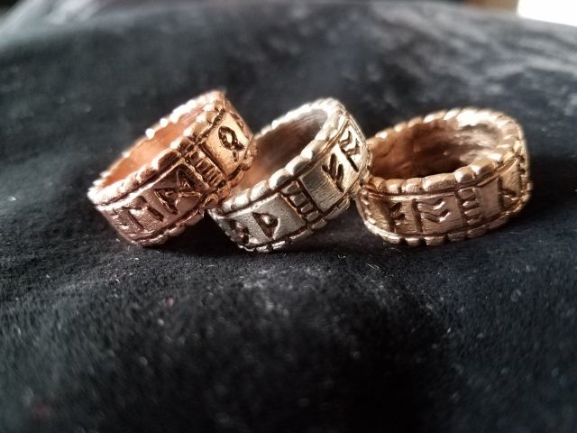 Three chunky metal rings, in copper, silver, and bronze, on a black background