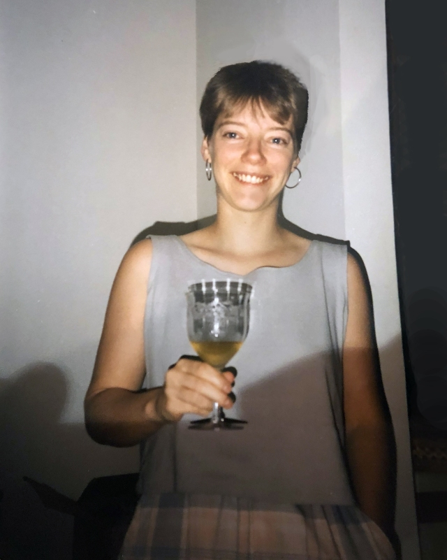 short-haired smiling woman in summer clothes holding glass of champagne and smiling