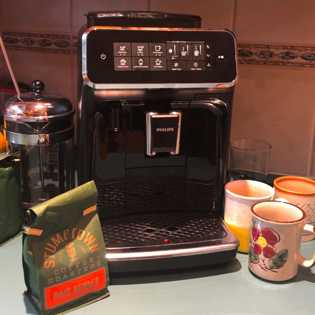 Photo of a super fancy espresso machine with beans and mugs