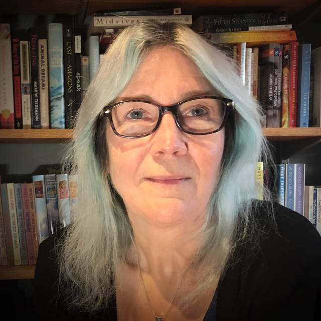 A woman with long silver-blue dyed hair and glasses sitting in front of bookshelves