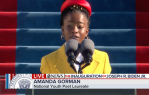 Young Black woman in red hat and yellow coat at a podium speaking into a double microphone.