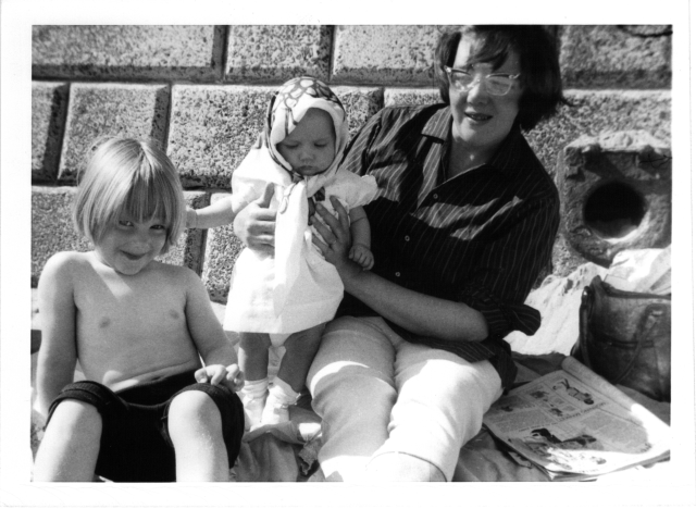 Black and white photo of mother, infant, and toddler on the beach
