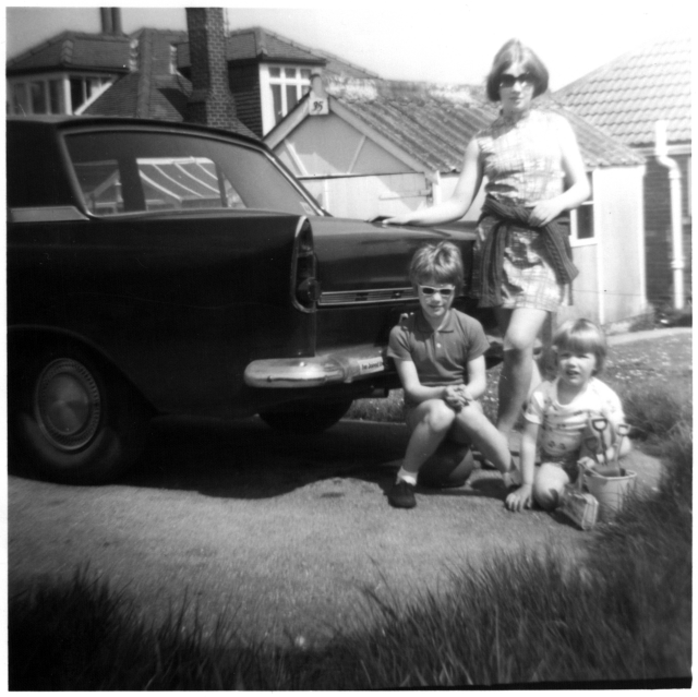 Black a white photo of a late 60s car parked in front of a holiday bungalow and three girls aged 14, 7, and 3