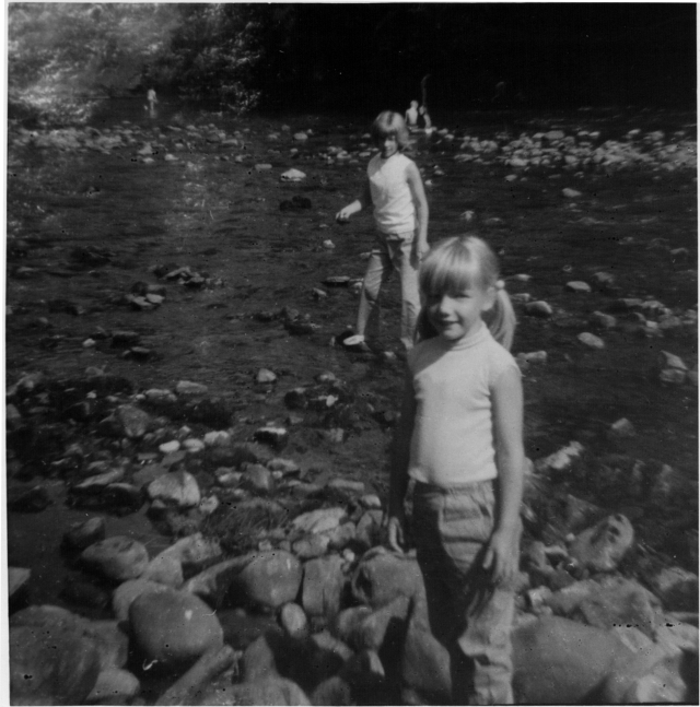 Black and white [photo of two girls standing in a river looking straight at the camera