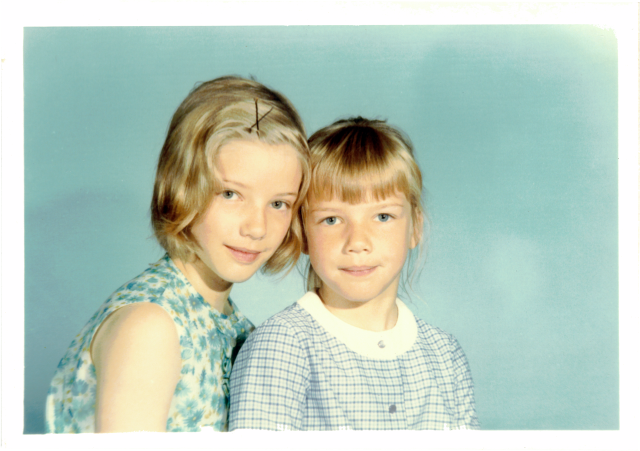 Colour photo of two sisters,both with blonde hair and blue eyes, against a professional hot background—aged 10 and aged 7
