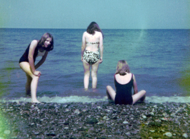 Colour photo of three girls on a beach, two in black swimsuits looking at each other, a third, in bikini staring at the horizon