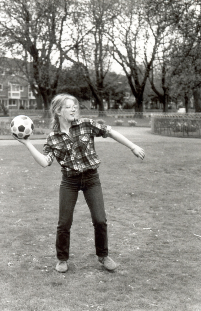Black and white photo of a long haired teenaged girl in glasses about to throw a football