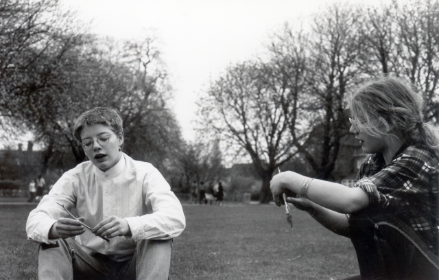 black and white photo of two sisters, one with short hair and one with long hair, in a park rolling cigarettes